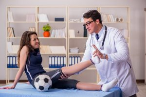 Girl Soccer Player With Sports Injuries At Physical Therapist