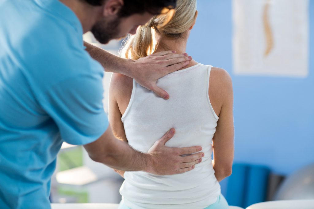 Physical Therapist in Idaho Falls touching woman's back