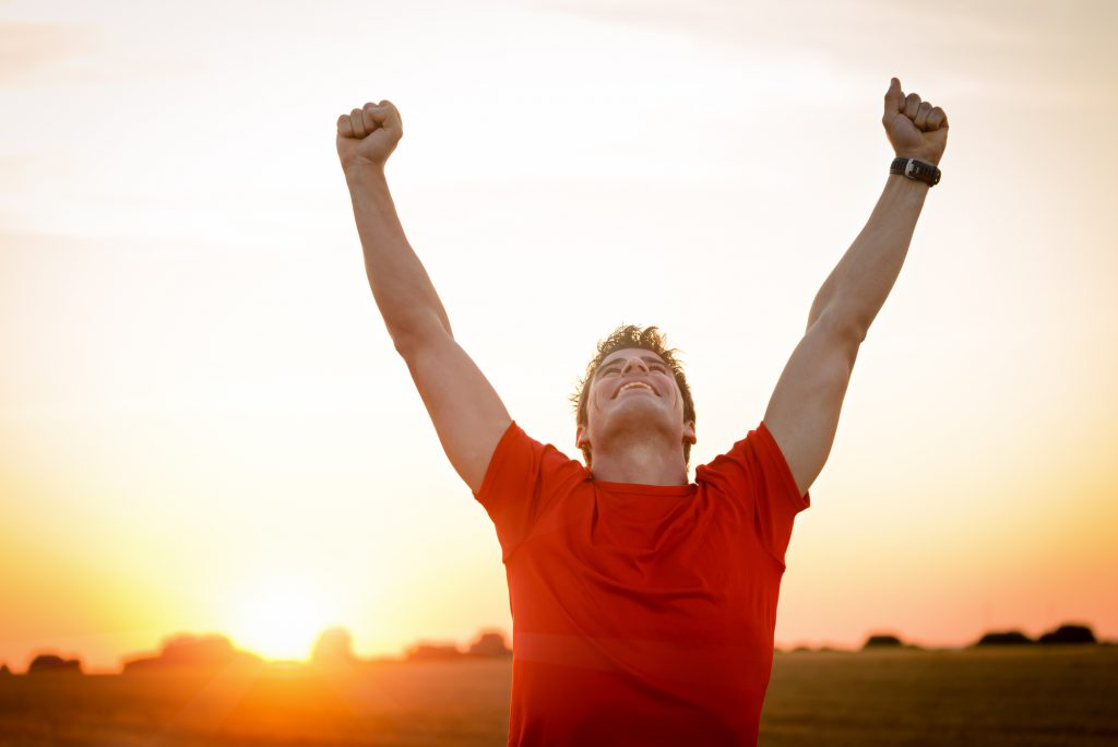 Male runner celebrating sports performance with arms raised